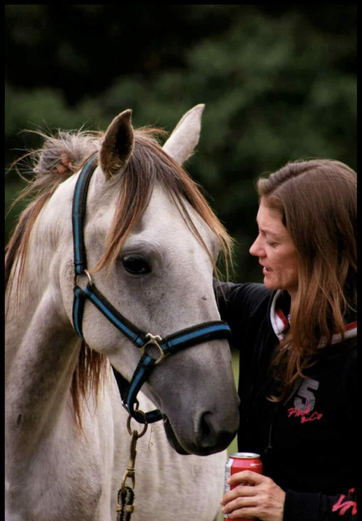 Veterinary technician standing next to a horse