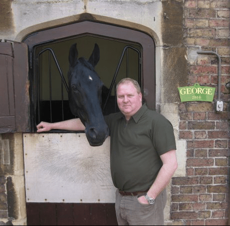 Large animal veterinarian standing next to a horse
