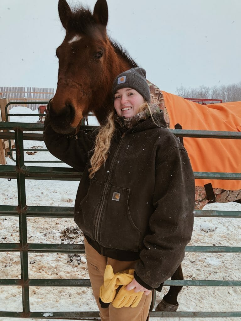 Veterinary Assistant standing next to a horse